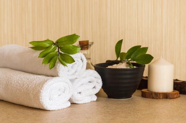 Serviettes, huile de massage cosmétique, feuille, sel de mer avec coquillages dans un bol noir et bougie sur un support en bois.