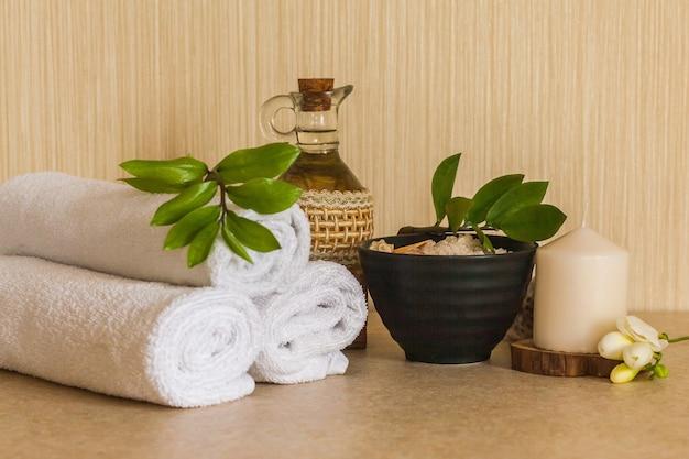 Serviettes, huile de massage cosmétique, feuilles, sel de mer avec des coquillages dans un bol noir et une bougie