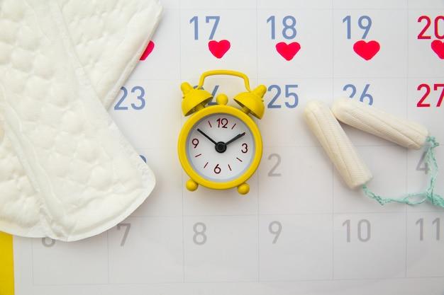 Serviettes hygiéniques, calendrier menstruel et horloges.