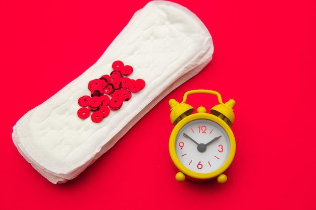 Serviettes hygiéniques et réveil sur rouge