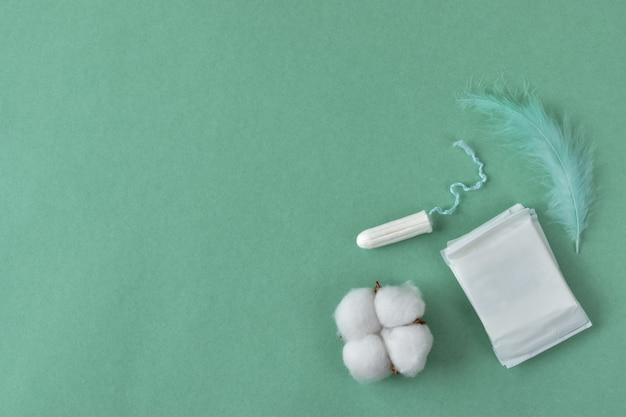 Serviettes hygiéniques et tampons pour femmes sur fond vert