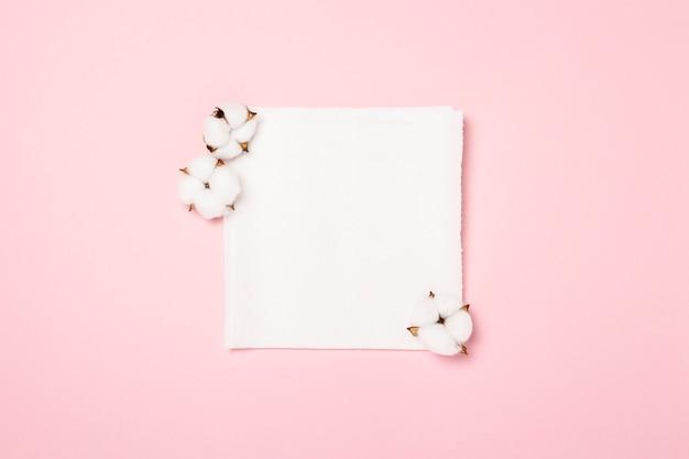 Serviettes en papier et fleurs en coton sur fond rose. bannière