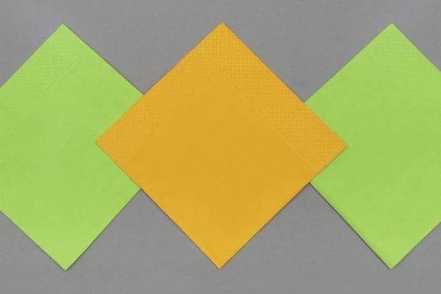 Serviettes en papier orange et vert sur fond de papier gris, vue de dessus.