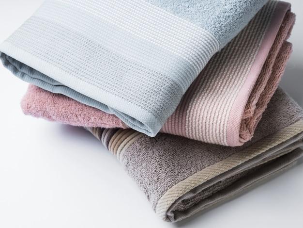 Serviettes pliées propres de couleur pastel sur blanc