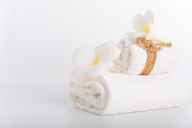 Serviettes roulées blanches décorer avec objet spa fleurs de frangipanier sur blanc