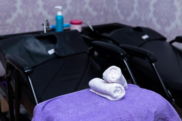 Les serviettes de spa turquoise s'empilent sur des fauteuils avec des supports de lavage dans un salon de coiffure.