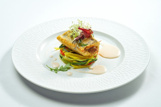 Servir de bar grillé avec des légumes dans une assiette blanche. isolé sur une surface grise.