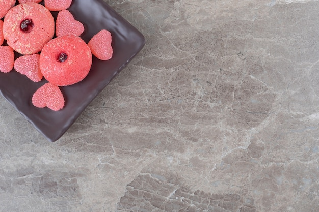 Servir des biscuits et des bonbons à la gelée sur un plateau sur une surface en marbre
