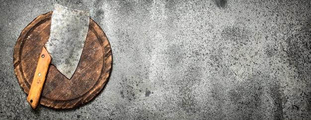 Servir de fond. ancienne hachette sur une planche à découper. sur fond rustique.