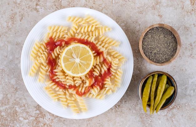 Servir des macaronis avec de petits bols de poivre noir et de poivrons marinés sur une surface en marbre.