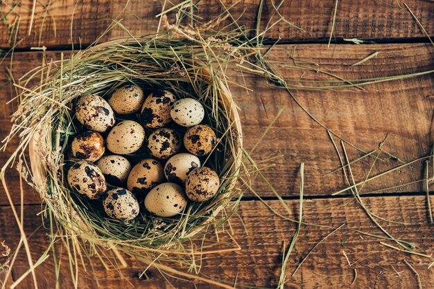 Servir des œufs frais. vue de dessus des œufs de caille se trouvant dans un bol avec du foin sur une table rustique en bois