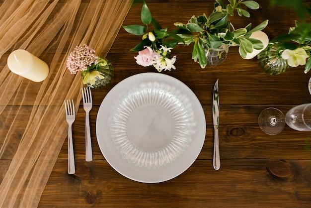 Servir une table de fête. belles assiettes et couverts, fleurs dans des vases sur une table en bois. vue de dessus