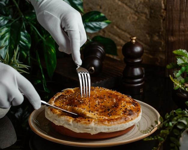 Un serviteur coupe soigneusement une tarte à la viande dans une assiette en poterie