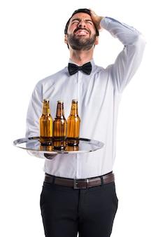 Serviteur frustré avec des bouteilles de bière sur le plateau