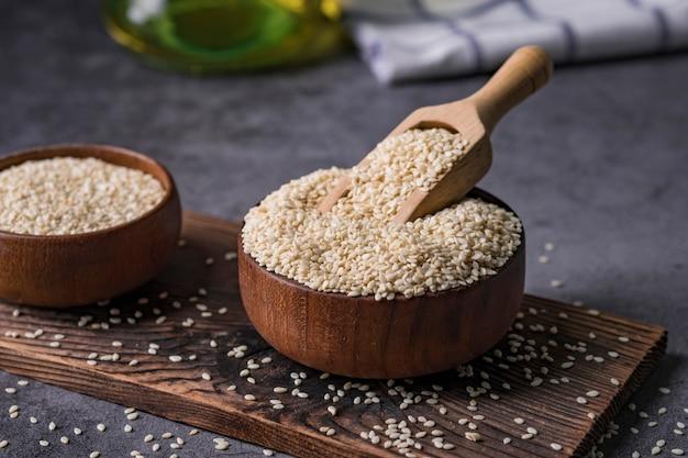 Sésame blanc dans une cuillère en bois sur une table sombre, huile de sésame dans le concept de pot et de graines.