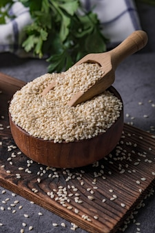 Sésame blanc dans une cuillère en bois sur une table sombre, huile de sésame en pot et graines.