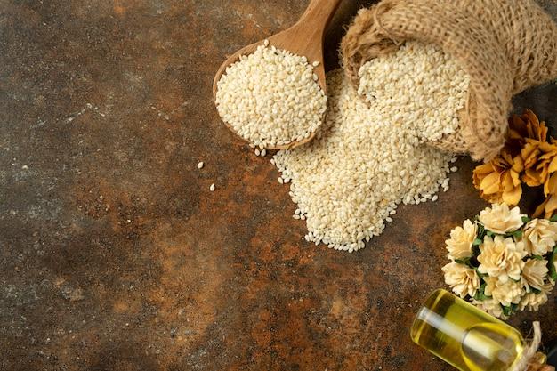 Sésame blanc et huile de sésame sur une cuillère en bois. sur la vue de dessus de fond rustique