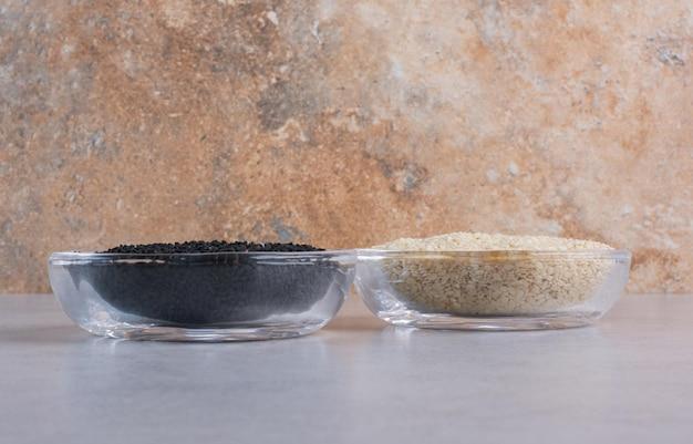 Sésame et cumin noir dans des coupes en verre.
