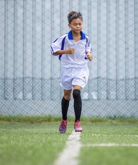 Session de formation de joueur de football garçon en cours d'exécution pour les enfants