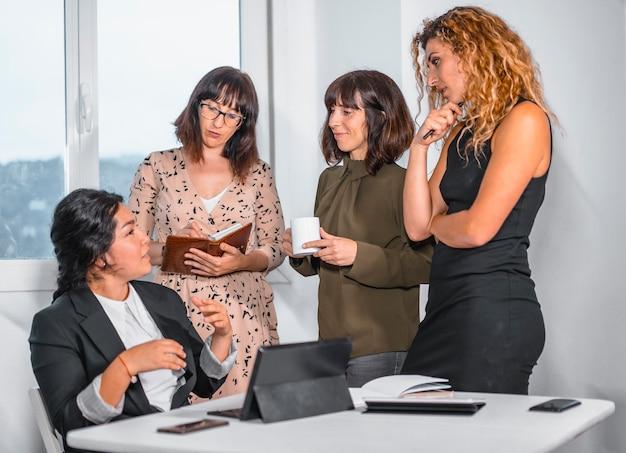Session jeunes entrepreneurs au bureau, chef d'un groupe ethnique latin et trois jeunes femmes caucasiennes préparant de futurs projets de travail
