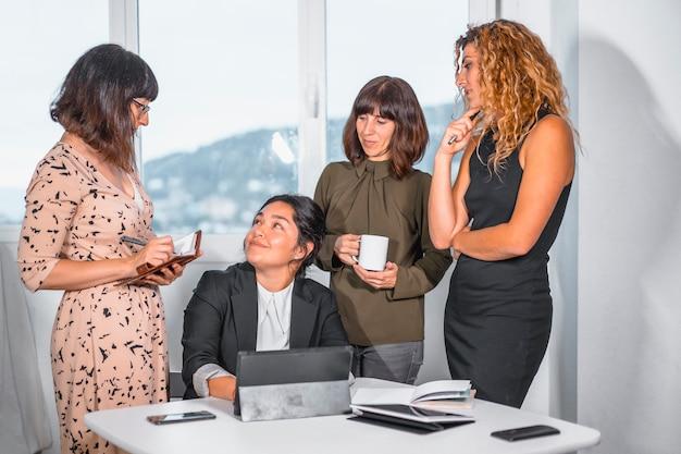 Session de jeunes entrepreneurs au bureau, chef d'un groupe ethnique latino assis et trois jeunes femmes de race blanche debout préparant de futurs projets de travail