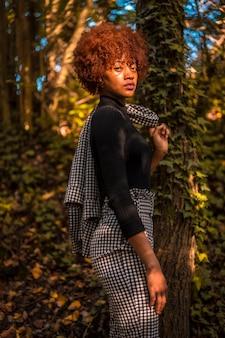 Session lifestyle d'un mannequin dominicain dans la nature en automne, regardant le sol