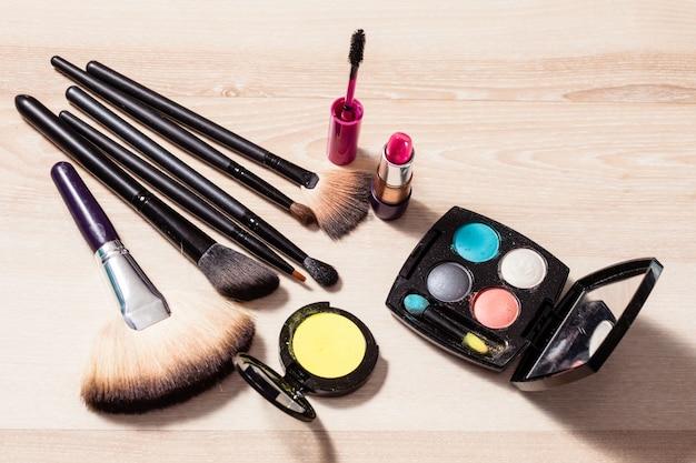 Set de maquillage : pinceaux et produits cosmétiques sur table en bois, gros plan
