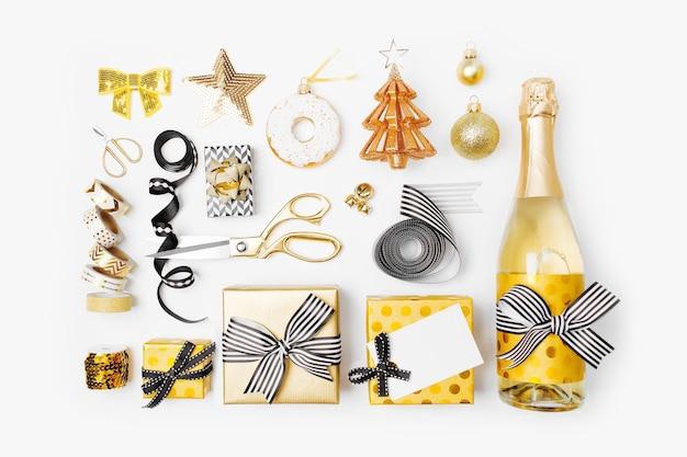 Set de noël à plat avec coffrets cadeaux, bouteille de champagne, nœuds, décorations et papier d'emballage aux couleurs or et noir. mise à plat, vue de dessus