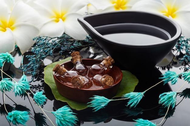 Set pour bol d'aromathérapie, bouteilles d'huile dans l'eau et fleurs de frangipanier. spa et détente.