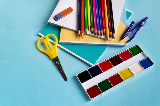 Set pour école de cahiers, ciseaux, crayons et aquarelles sur bleu