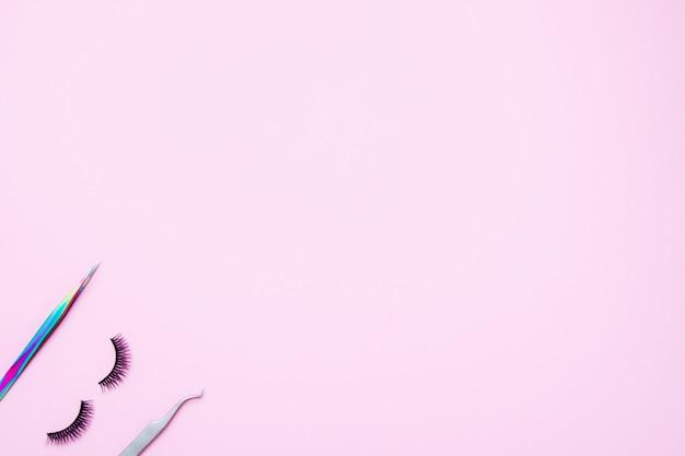 Set pour l'extension des cils sur fond rose. concept beauté beauté. faux cils et pinces