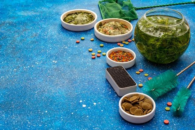 Set pour le soin des poissons d'aquarium. aliment assorti, algues vertes, filet à papillons, grattoir, brosses. fond de mer bleu marine