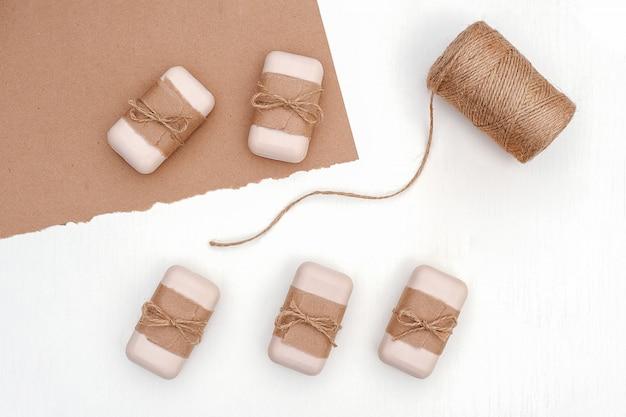 Set de savon décoré avec du papier kraft et une pelote de ficelle sur fond blanc