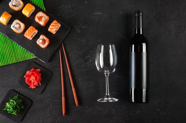 Set de sushi sashimi et sushi, bouteille de vin et un verre sur ardoise