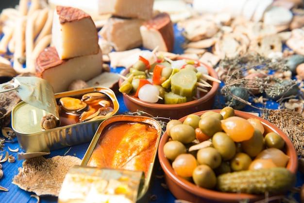 Set de table avec un apéritif composé de différents aliments fromages et conserves de cornichons