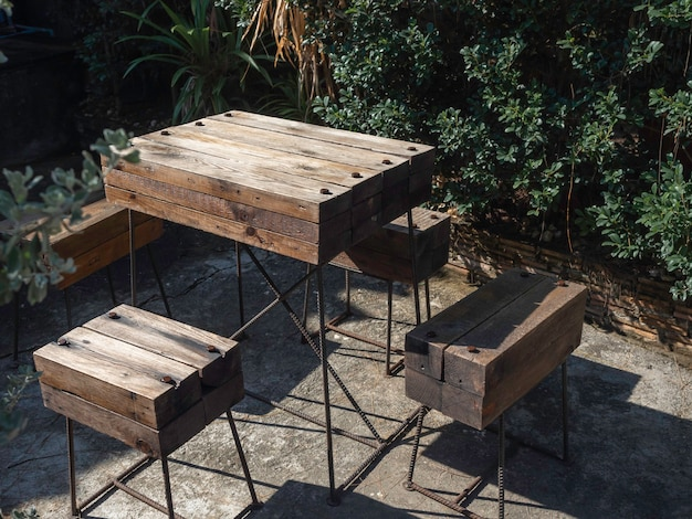 Set de table en bois. table et chaises vides faites de planches de bois massif audacieuses assemblées avec une décoration de barre en acier noir sur un sol en béton dans le jardin extérieur.