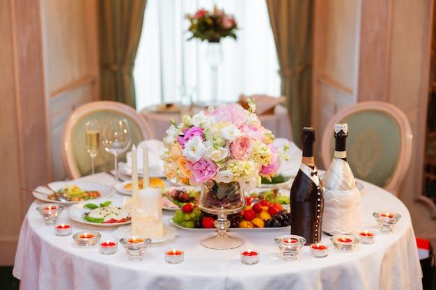 Set de table pour banquet de mariage avec des bougies allumées.