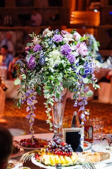 Set de table pour banquet de mariage avec composition florale de dianthus décoratif.