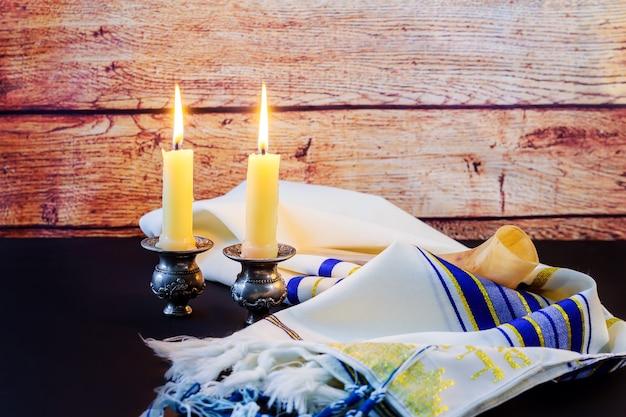 Un set de table pour shabbat avec des bougies allumées, du pain challah et du vin.