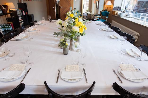 Set de table avec des roses jaunes pour une fête festive