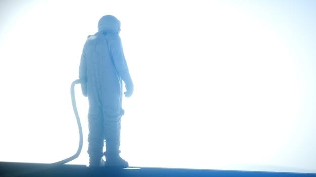Seul astronaute dans un intérieur futuriste à la recherche dans l'immense fenêtre