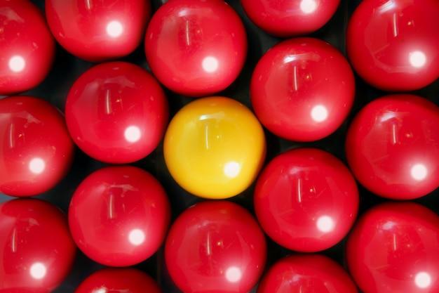 Seul ballon de billard jaune entre plusieurs boules rouges