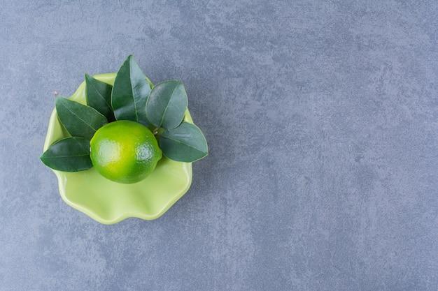 Un seul citron avec des feuilles dans un bol sur une table en marbre.
