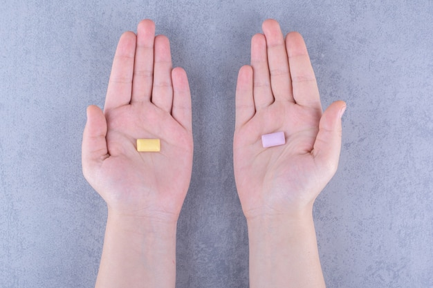 Un seul comprimé de chewing-gum dans chaque main sur une surface en marbre