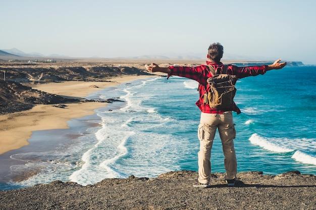 Seul, heureux, voyageur, à, sac à dos, gens, homme, apprécier, les, destination, place, plage, debout, sur, a, falaise, et, ouverture bras, pour, succès, et, joyeux, concept