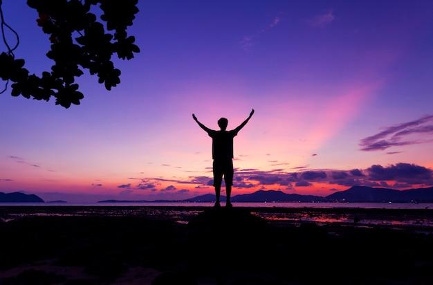 Seul homme debout, levant sa main et voir la vue de paysage au coucher du soleil