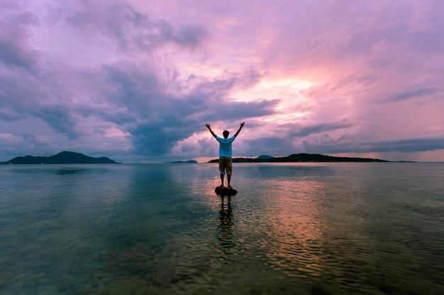 Seul homme touriste debout sur la pierre en mer tropicale et admirant les paysages