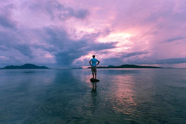 Seul homme touriste debout sur la pierre en mer tropicale