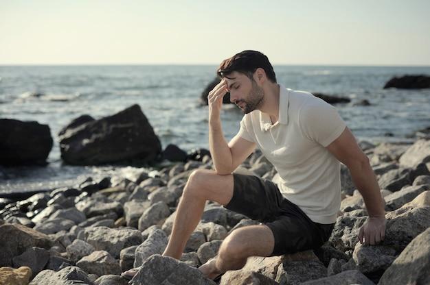 Seul homme triste assis sur une plage de la mer, en plein air