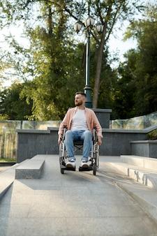 Seul jeune homme en fauteuil roulant dans les escaliers, problème d'impuissance et de handicap. personnes paralysées et difficultés de handicap, dépassement du handicap. personne de sexe masculin handicapé marchant dans le parc